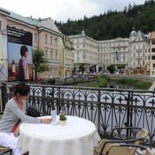 Karlovy Vary'nin ortasındaki derenin üzerinde masallardaki gibi bir köprü ve köprünün üzerindeki kafenin masa ve sandalyeleri kahve keyfi için harika.